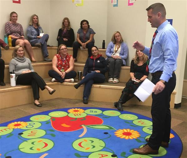 Principal Michael McConnell shares the certification news with staff members.