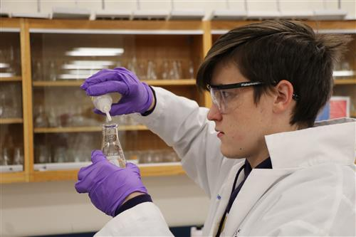 Student wearing gloves and googles pours solution into a beaker