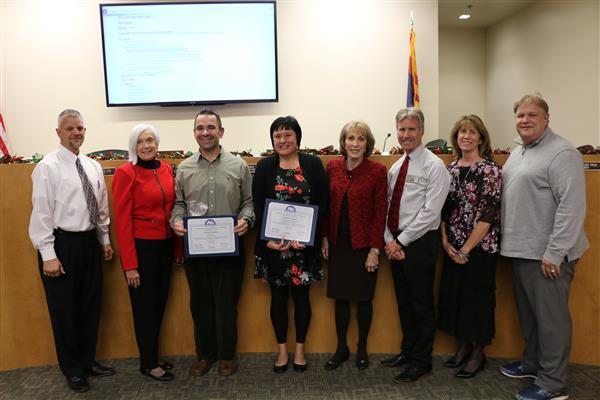 Governing board stands with the two December Distinguished Service Award recipients