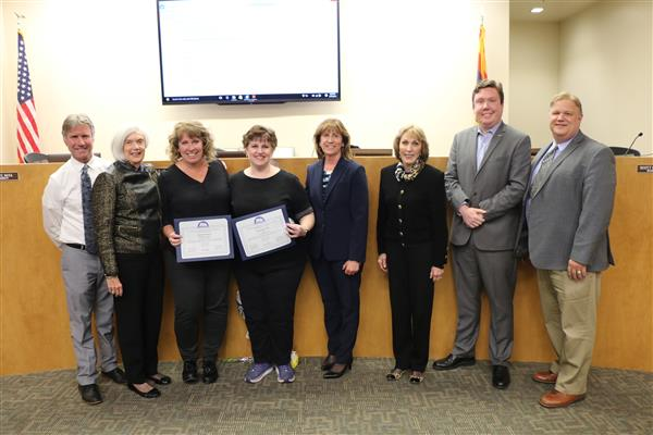 Governing board stands with two Distinguished Service Award recipients